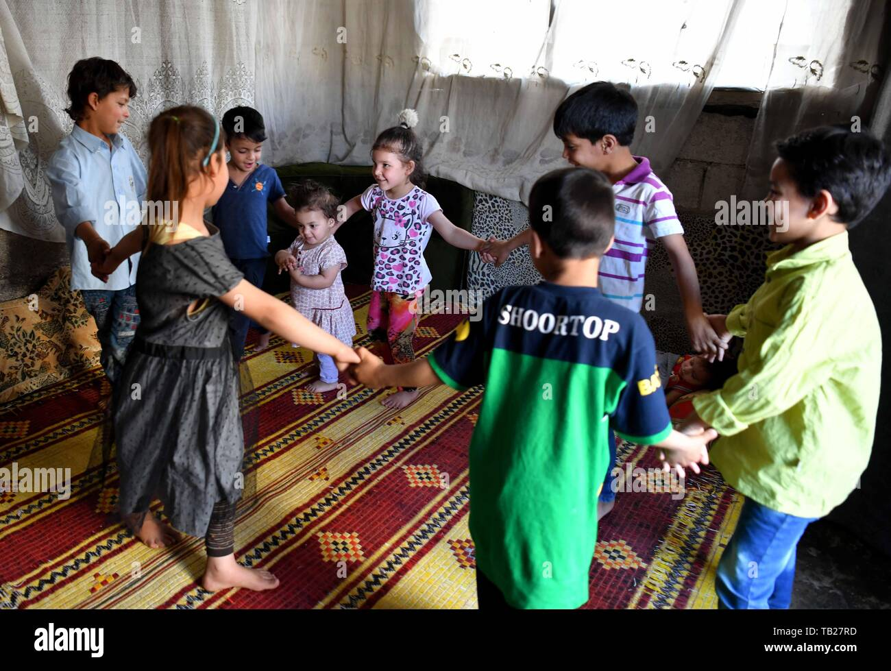"""Damascus, Syria. 28th May, 2019. Ibrahim Mossa (1st R) plays with his siblings and cousins in the Jaramana suburb of Damascus, Syria, on May 28, 2019. For Hussain Mossa, whose childhood was peaceful and worth remembering, his son Ibrahim is not so lucky as him. Hussain's older son, Ibrahim, was born in 2011 when the Syrian crisis began. In Syria, those who were born during the war were regarded as """"Generation of War."""" They were unable to have a normal or healthy childhood like many of their parents did. Credit: Ammar Safarjalani/Xinhua/Alamy Live News Stock Photo"""
