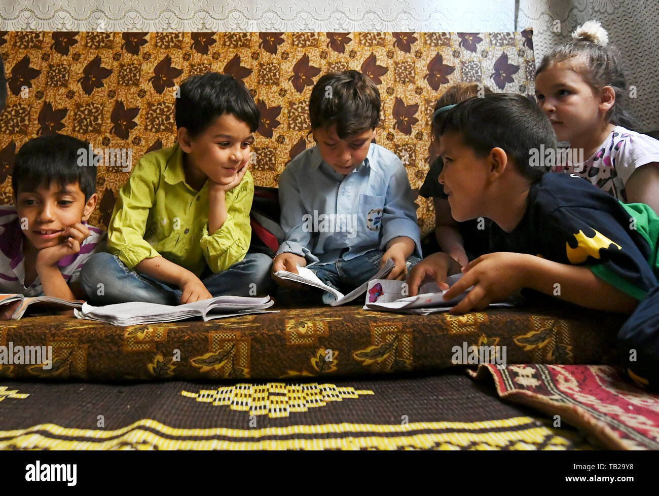 """Beijing, Syria, China. 28th May, 2019. Ibrahim Mossa (2nd L) smiles while sitting with his siblings and cousins in an unfinished house in the Jaramana suburb of Damascus, Syria, on May 28, 2019. Ibrahim was born in 2011 when the Syrian crisis began. In Syria, those who were born during the war were regarded as """"Generation of War."""" They were unable to have a normal or healthy childhood like many of their parents did. Credit: Ammar Safarjalani/Xinhua/Alamy Live News Stock Photo"""