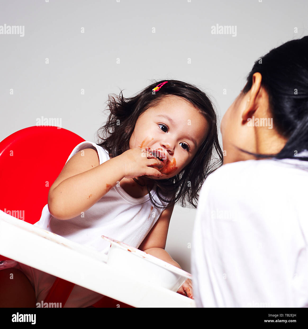 Asian mother feeding a super adorable cute baby girl chocolate in her high chair and she is making a mess Stock Photo