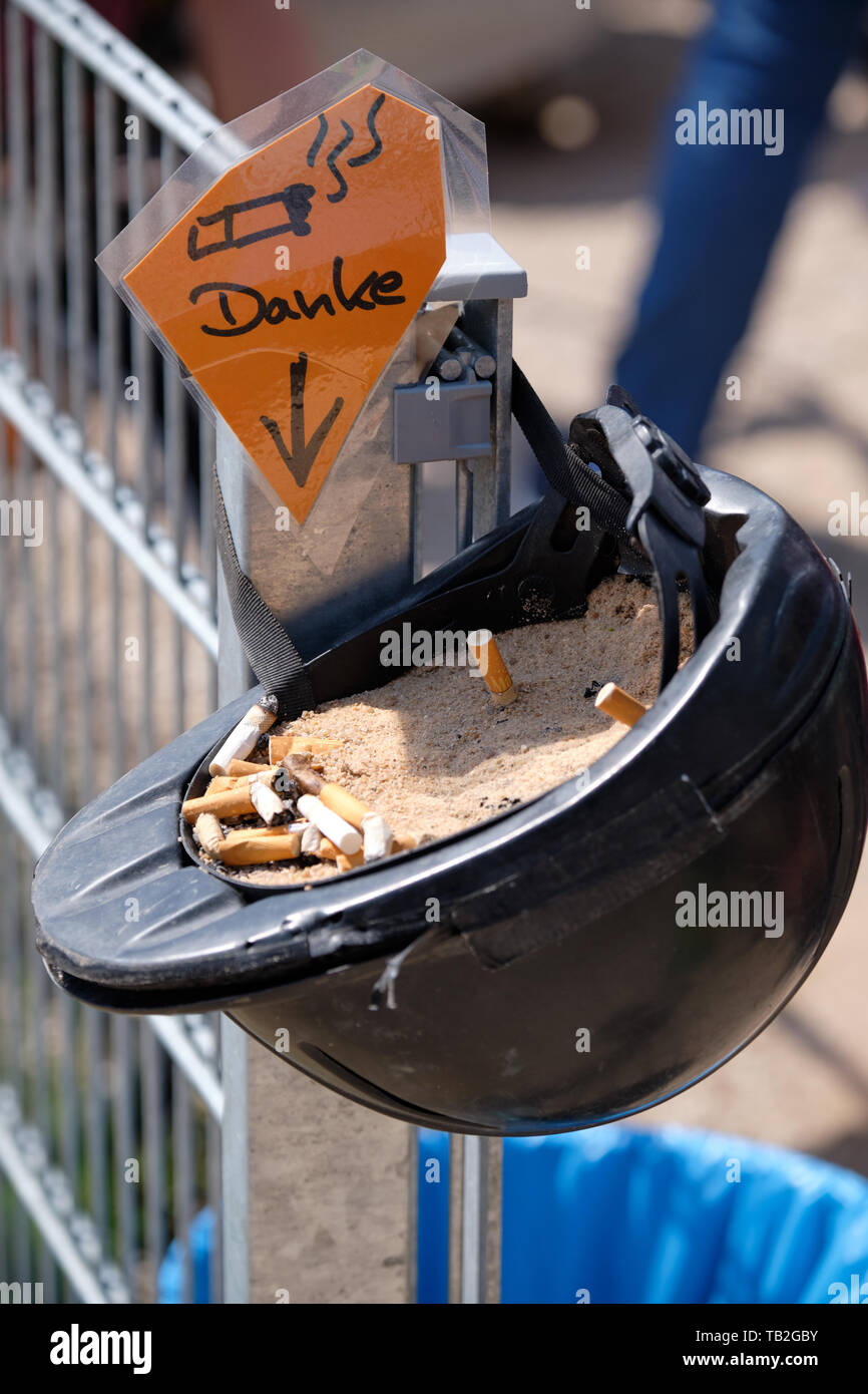 An old riding helmet with sand and cigarette ends in it is being used as an ashtray with a sign saying 'Danke' (thanks) - Stock Image