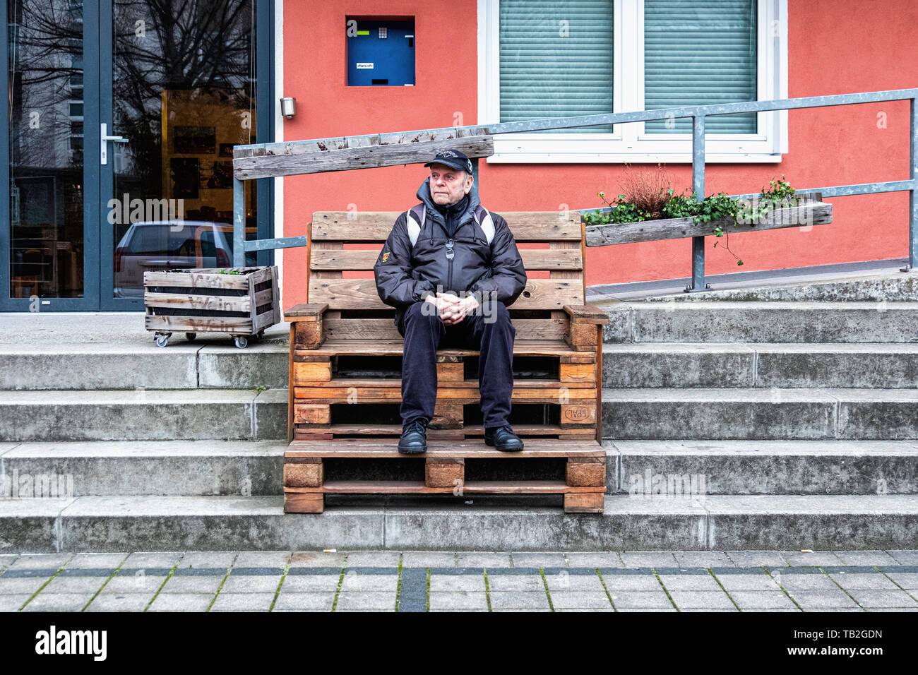 Schöneberg-Berlin. Elderly man sitting on wooden Bench made of recycled wood outside YNot cafe & bar. Reclaimed old wood palettes. - Stock Image