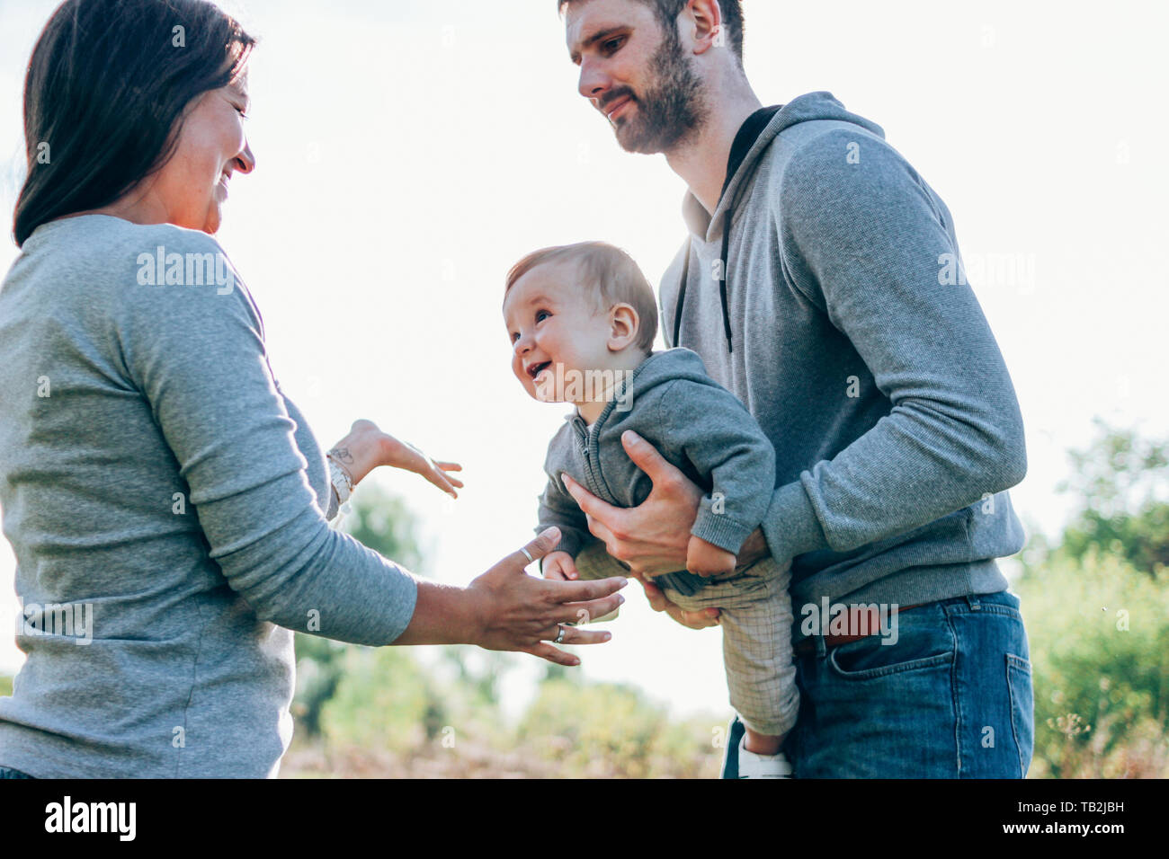 Happy family with cute baby boy on sky background outdoors sensitivity to nature concept