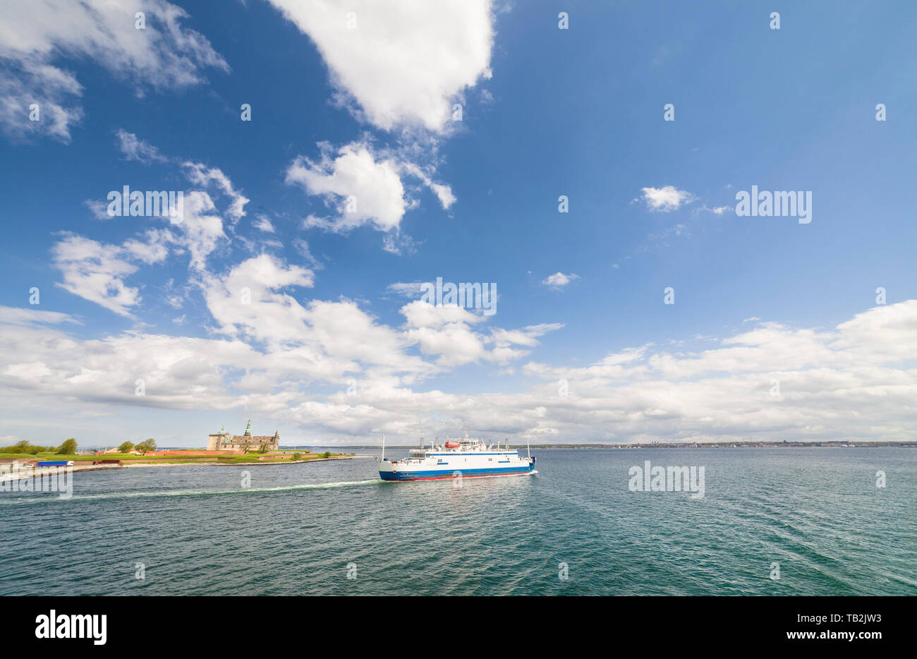 Car ferry to Helsingborg, Sweden, leaving the port of Helsingor, Denmark, with the Kronoborg castle in the background. Logos and brandings removed. - Stock Image