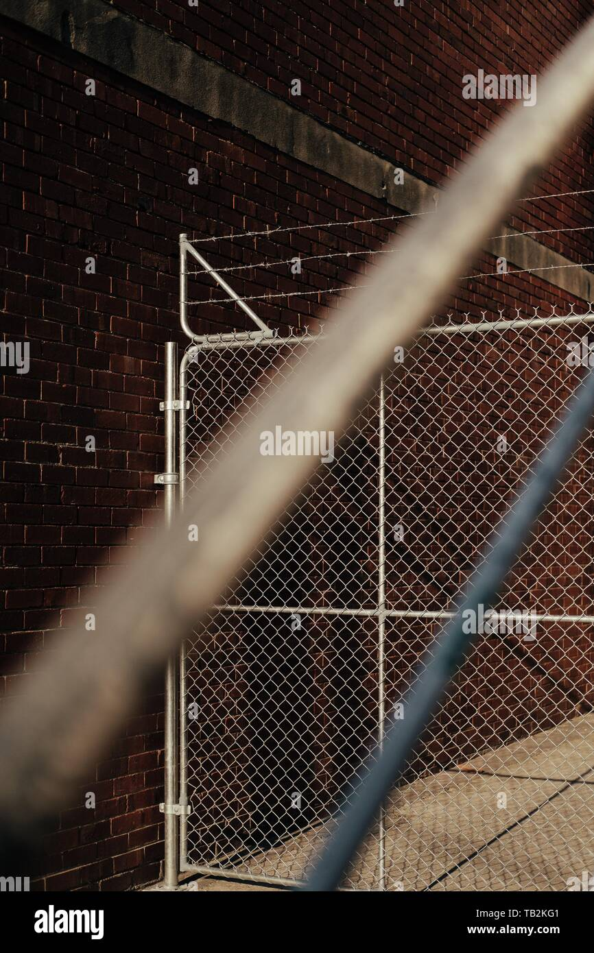 Barbed wire with a fence and blurred staircase handle in the front - Stock Image