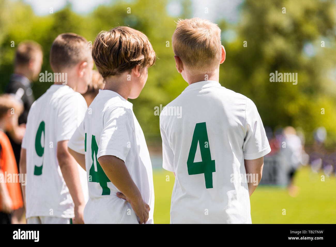 Children Sports Team Members. Junior Soccer Players on Substitution Bench. Kids in White Jersey Shirts with Green Numbers on its Back - Stock Image
