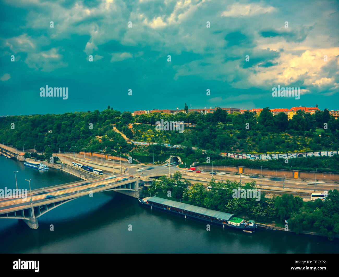 aerial view of metronome next to Vltava river sunny day dark clouds - Stock Image