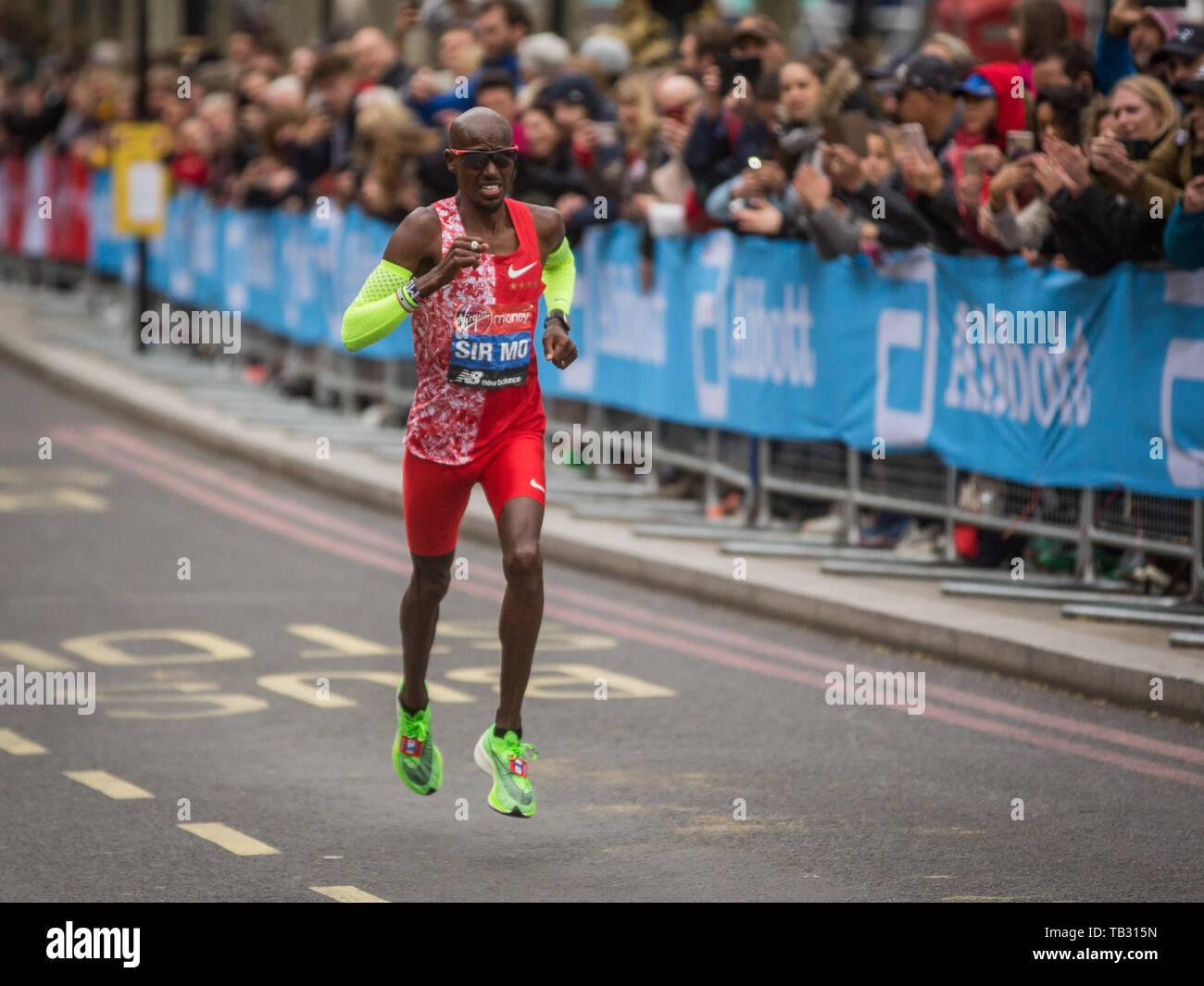 Sir Mo Farah running in the 2019 Virgin Money London Marathon passing along the Embankment towards the finish line on the Mall.  Featuring: Sir Mo Farah Where: London, United Kingdom When: 28 Apr 2019 Credit: Wheatley/WENN - Stock Image