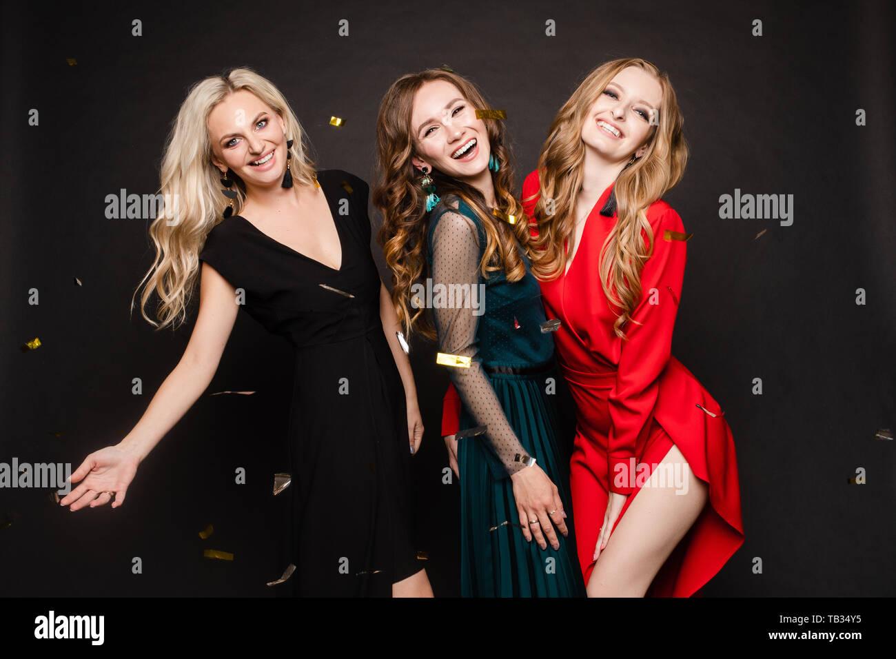 Three gorgeous ladies in evening dresses having fun on black background. Stock Photo