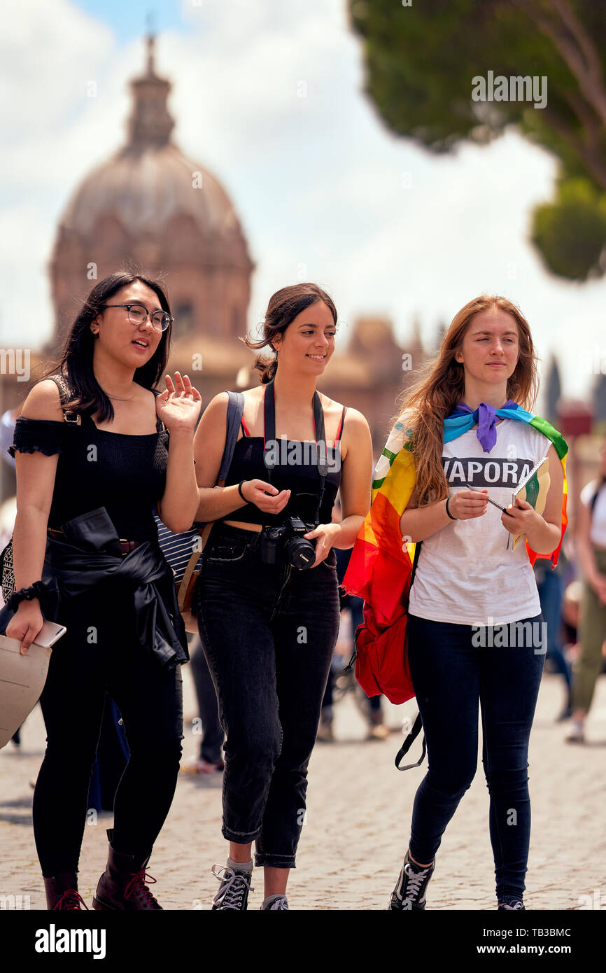 Juvenile tourism in Rome, Italy. Three happy young girls (Asian, Spanish, German/French) walking in front of a stunning church dome on a hot sunny day Stock Photo