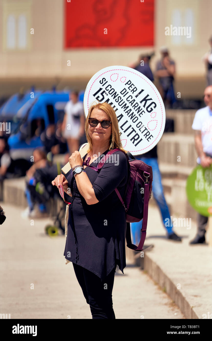 Rome, Italy: Lady near the Colosseum with placard reading: 'Every kilogram of meat over 15,000 litres of water are consumed'. Global Strike for Future - Stock Image