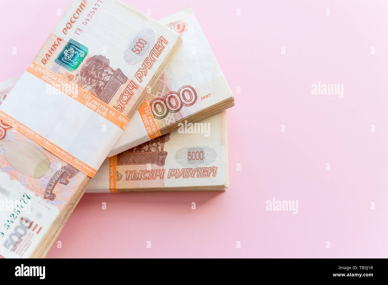 Stack of 5000 rubles packs isolated on pink. The concept of wealth, profits, business and finance. Stack money in the five thousandth bills banknotes Stock Photo