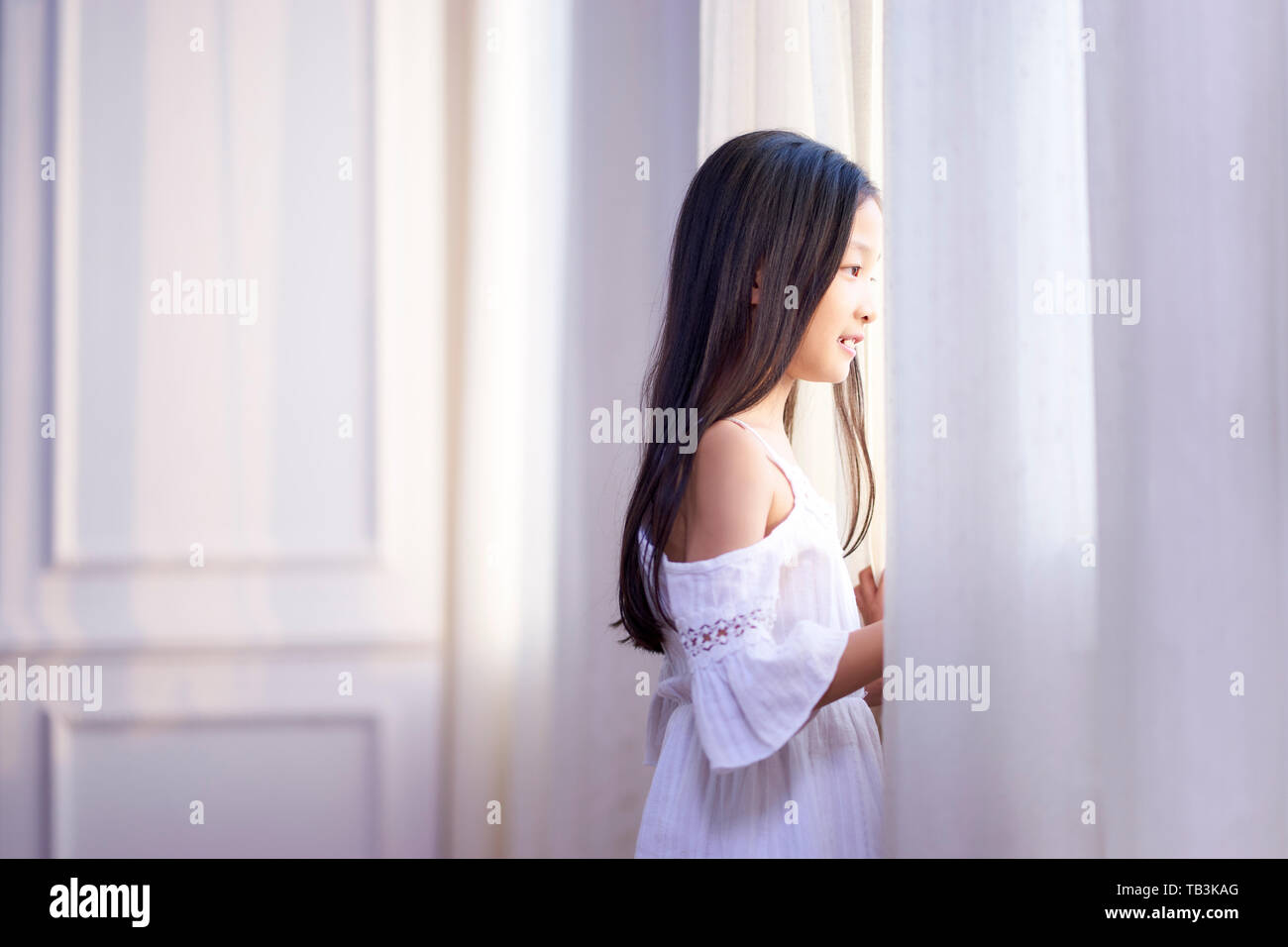 Beautiful Little Asian Girl With Long Black Hair Looking Out Of Window In Bedroom Stock Photo Alamy