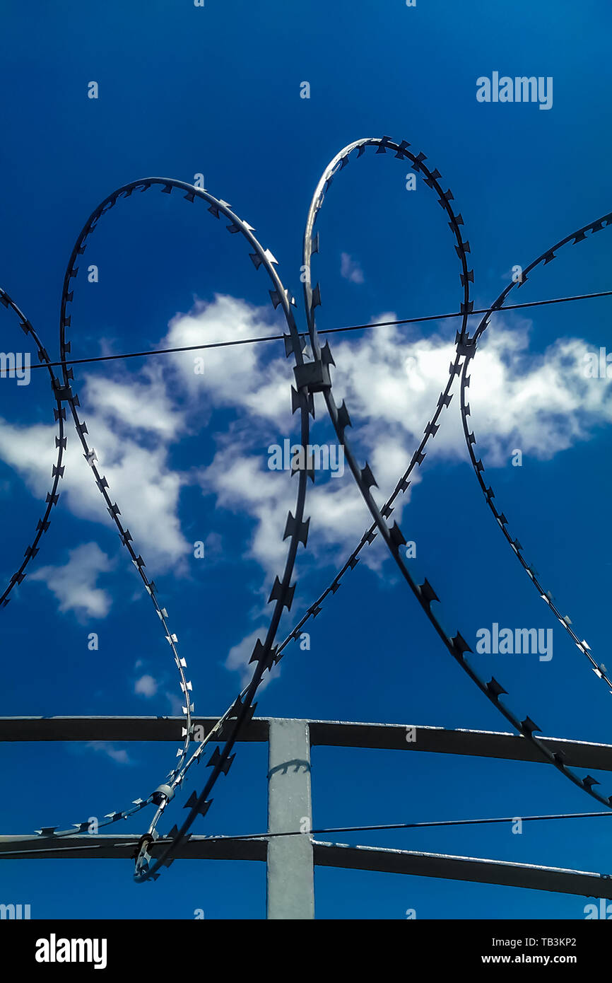 Closeup view of barbed wire fence forming a shape of heart on blue cloudy sky background. Soul barbed wire. Symbol danger warning. Frame of war and pe - Stock Image
