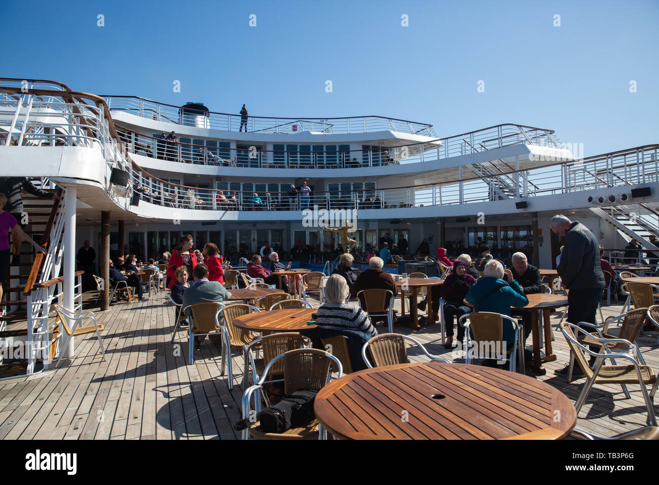 Passengers enjoy the sunshine on the aft outer decks of the Marco Polo in The North Atlantic Ocean Stock Photo
