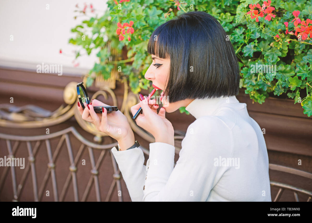 Girlish secrets concept. Woman making makeup with pocket mirror. Check if everything is right before date. Makeup concept. Girl brunette with lipstick looking in mirror check her makeup appearance. - Stock Image