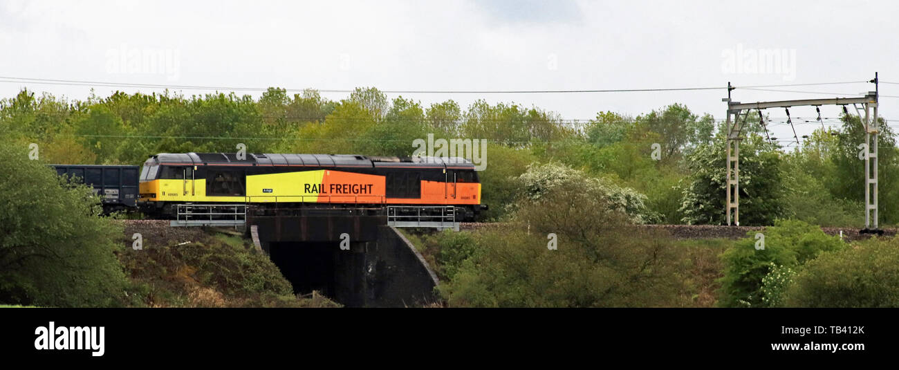 A GBRF, GB Railfreight, diesel locomotive passing Abram near Bamfurlong Junction on the West Coast main line pulling a train of empty stone wagons. - Stock Image