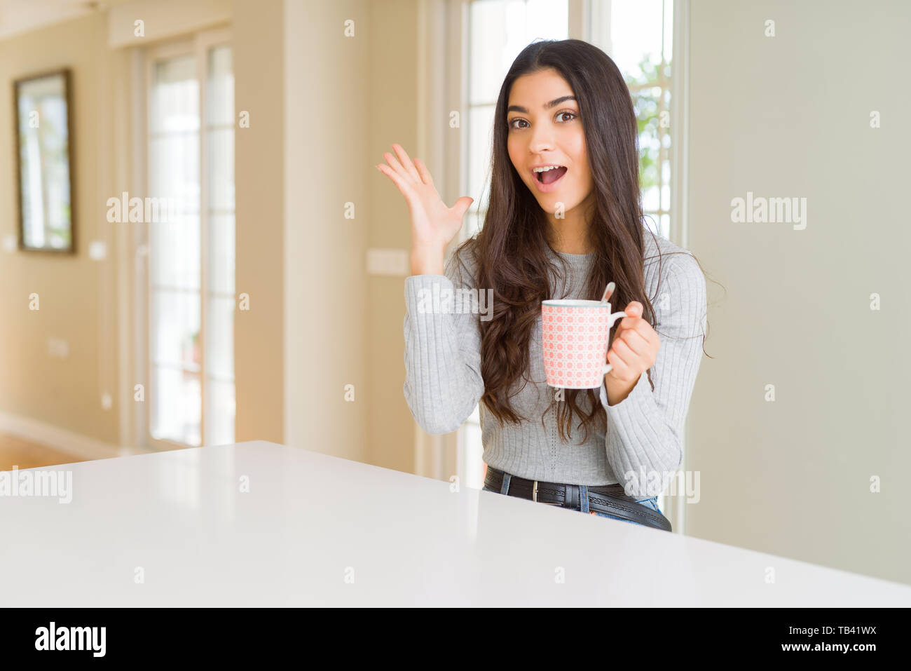 d67f0a433b6 Young woman drinking a cup of coffee very happy and excited, winner  expression celebrating victory screaming with big smile and raised hands