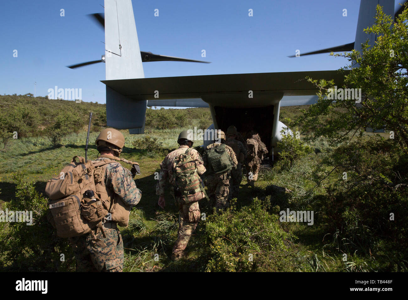 U.S. Marines with Special Purpose Marine Air-Ground Task Force-Crisis Response-Africa 19.2, Marine Forces Europe and Africa, and members of the Italian military board a U.S. Marine Corps MV-22B Osprey while conducting a raid rehearsal during exercise Joint Stars 2019 at Perdas range in Sardinia, Italy, May 24, 2019. Joint Stars 2019 is a bilateral training exercise between the Italian Armed Forces and U.S. Marines. SPMAGTF-CR-AF is deployed to conduct crisis-response and theater-security operations in Africa and promote regional stability by conducting military-to-military training exercises t Stock Photo