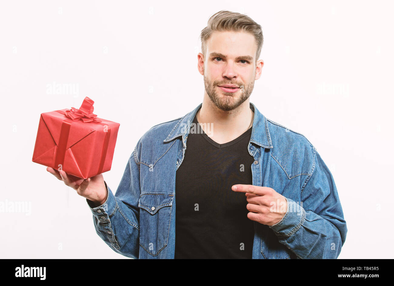 Hipster denim shirt hold gift box white background. Love and romantic feelings concept. Man with beard and happy face celebrate valentines day. Valentines day gift. Gift for girlfriend. Romantic gift. - Stock Image