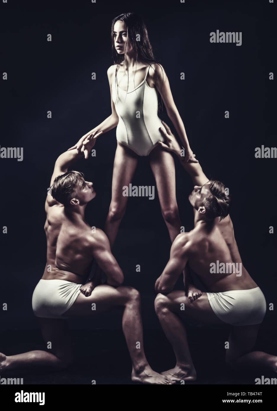 acrobatics workout of three friends. acrobatics people train in white sportswear. - Stock Image
