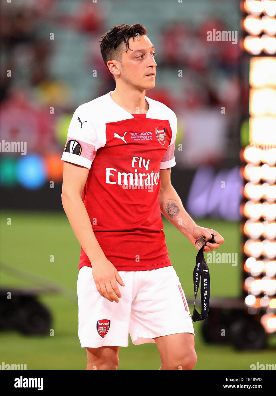 Arsenal's Mesut Ozil takes off his runners-up medal after the UEFA Europa League final at The Olympic Stadium, Baku, Azerbaijan. - Stock Image