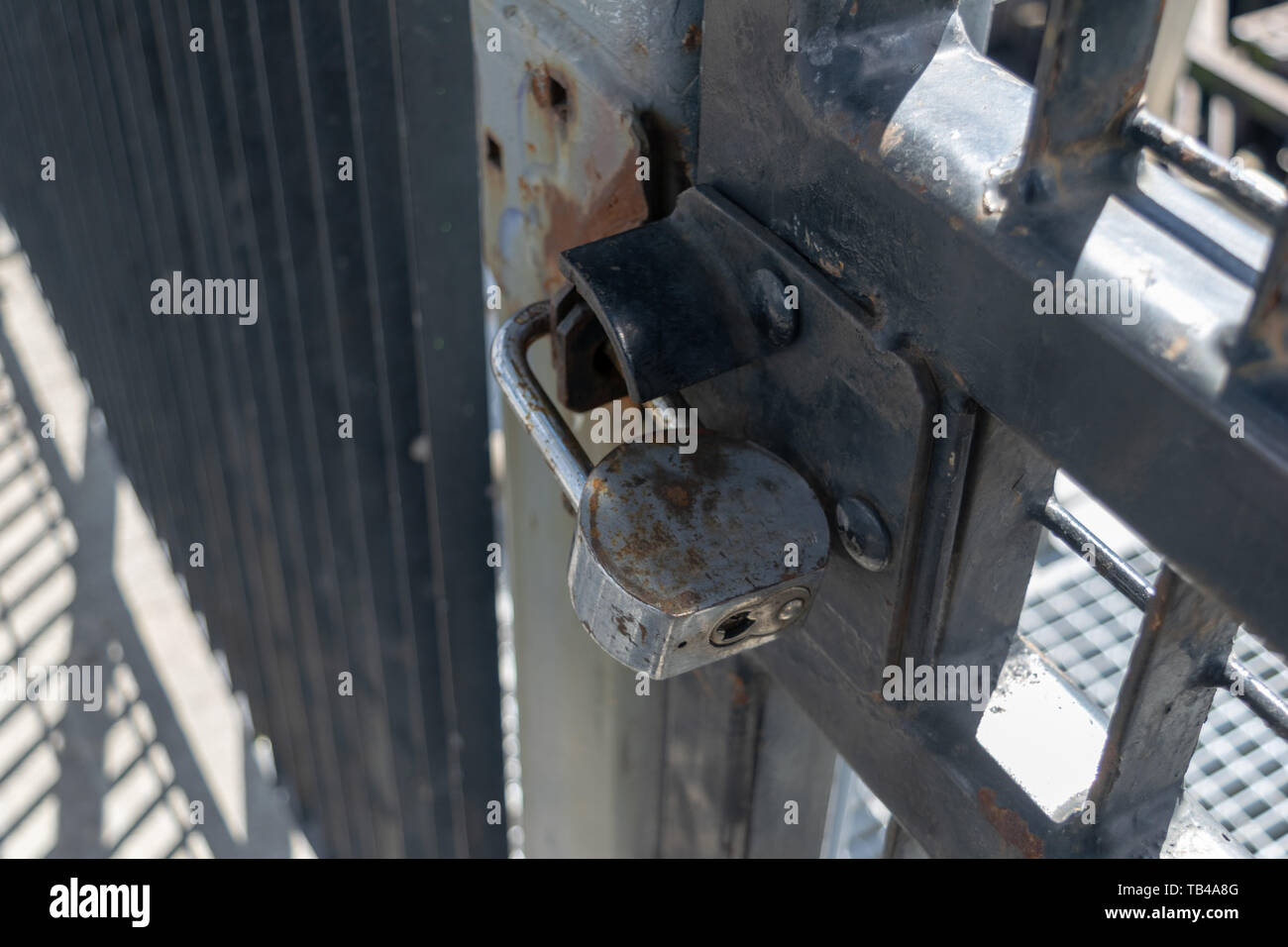 Old and rusty heavy duty pad lock securing aan iron gate, close-up - Stock Image