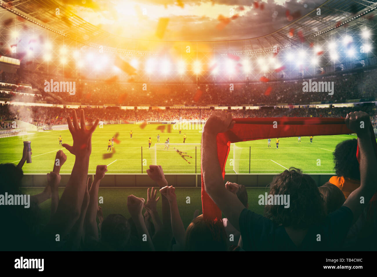 Football scene at night match with with cheering fans at the stadium - Stock Image