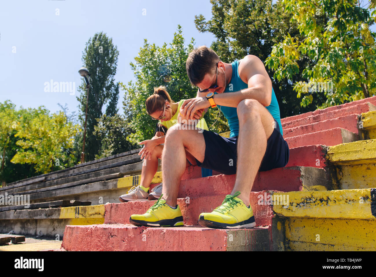 Runners in the city park resting after jogging and listening to music - Stock Image