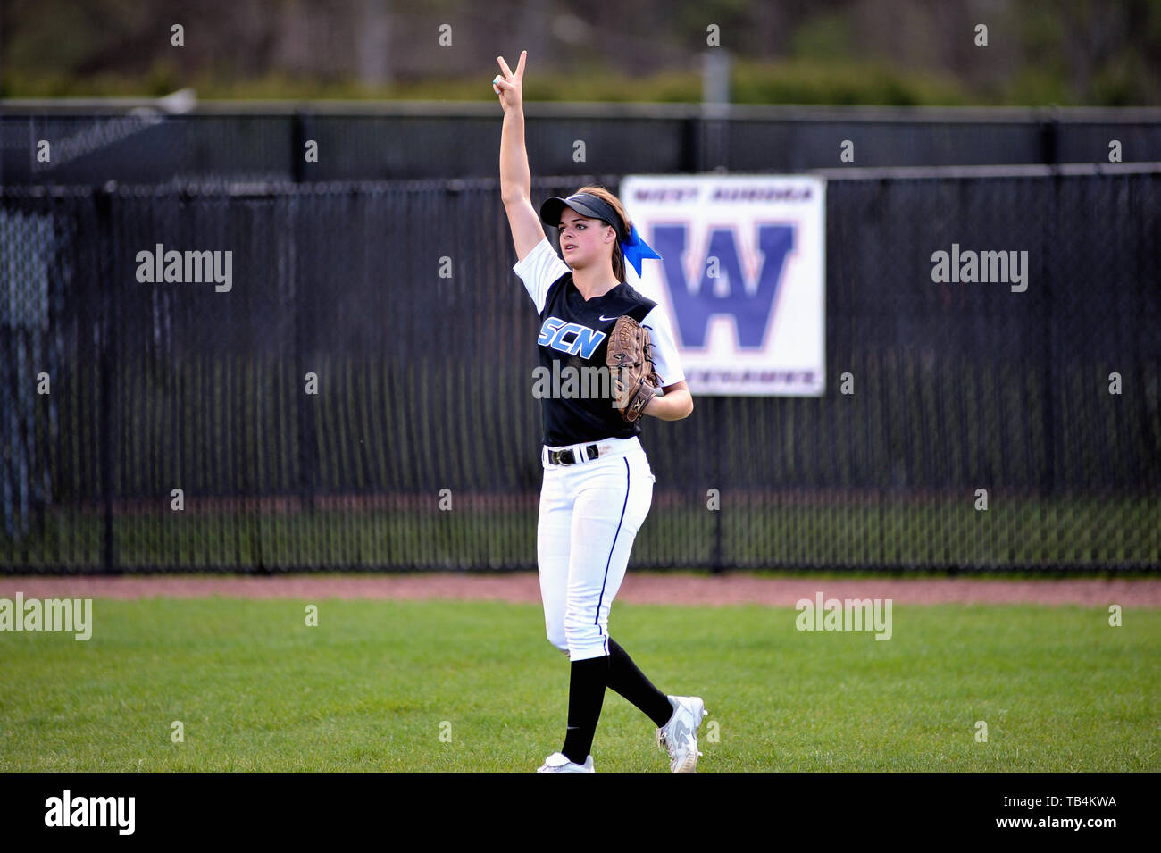 An outfielder exchanging hand signals and communicating with teammates that there are two outs in the inning. USA. - Stock Image