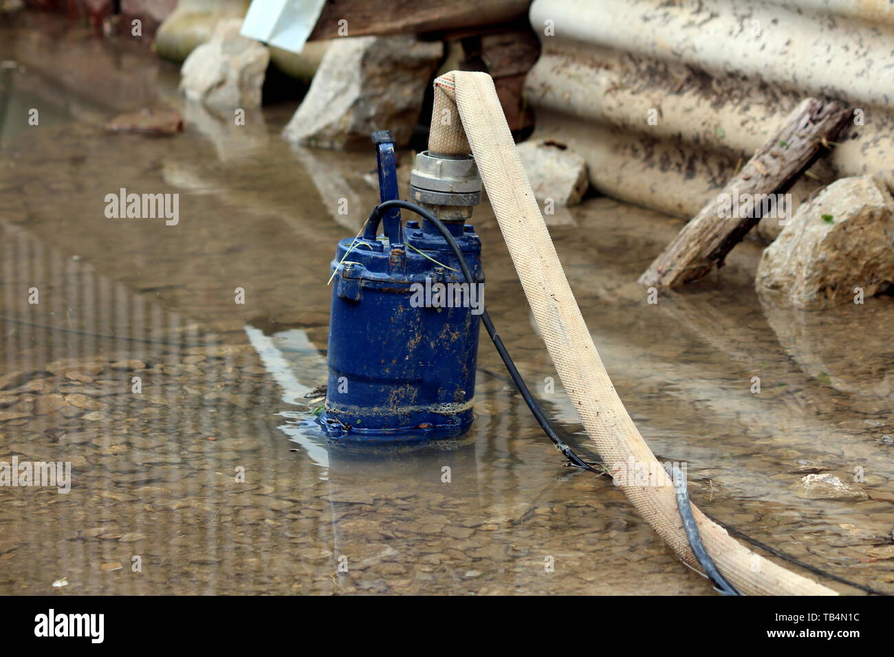 Heavily used old partially submerged metal water pump pumping water from flooded backyard through fire hose surrounded with rocks and gravel - Stock Image