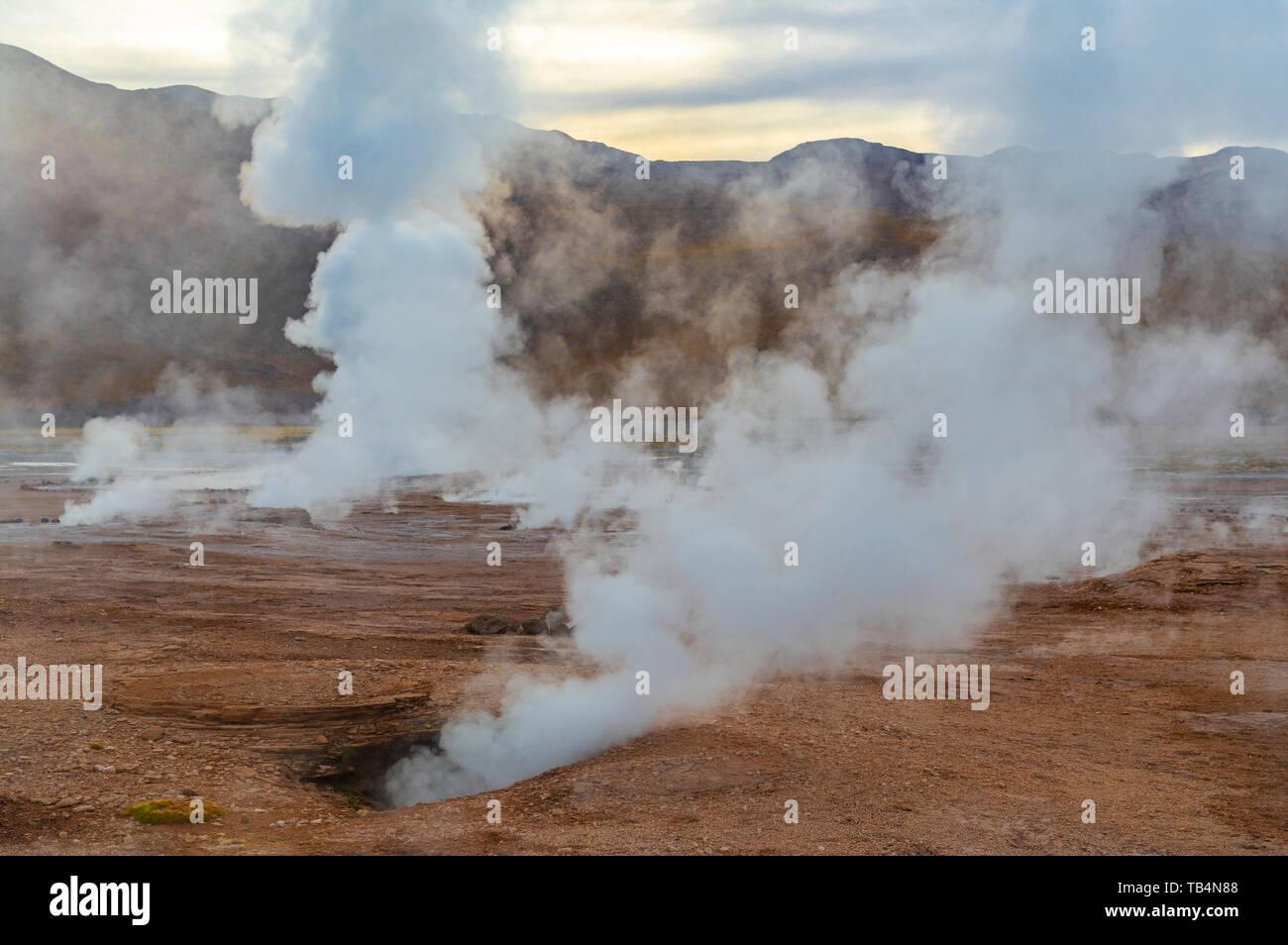 Landscape of the Tatio Geysers with its fumaroles and vapor trails at sunrise, Atacama Desert, Chile. - Stock Image