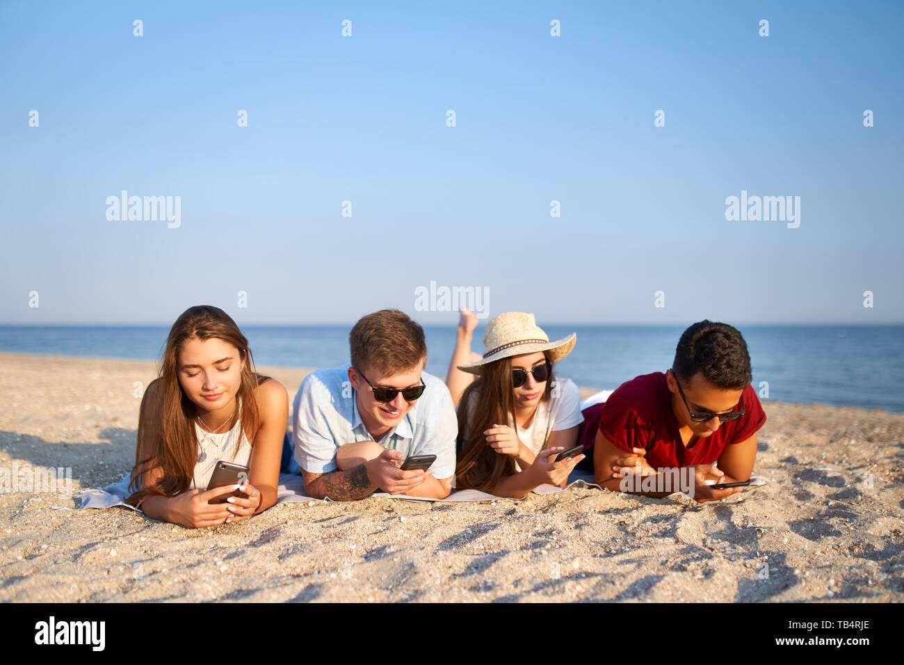 Group of millenials using smartphones laying together on beach towel near sea on summer sunset. Young people addicted by mobile smart phones. Always - Stock Image