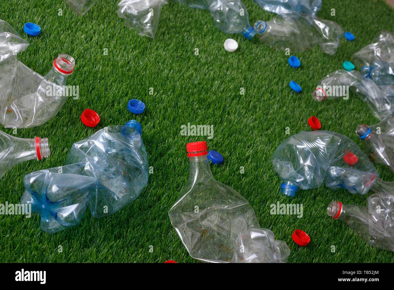 The concept of recycling plastic and environmental protection. Pet preforms for plastic bottles on the green grass. Artificial turf, plastic. - Stock Image