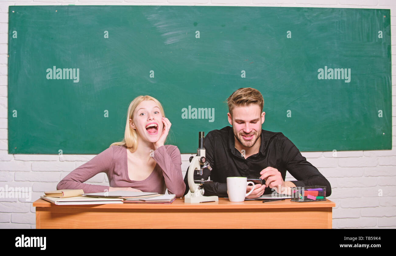 Scientific experiment. Guy and girl at desk with microscope. Studying in college or university. Biology lesson. Students studying university. Genetics and engineering. Difficult university subject. - Stock Image