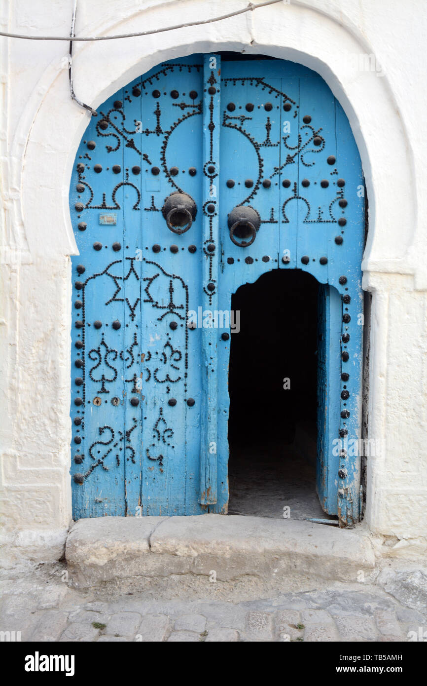 The traditional blue door of a 17th century house decorated with Islamic motifs in an alleyway of the medina (old city) of Tunis, Tunisia. Stock Photo