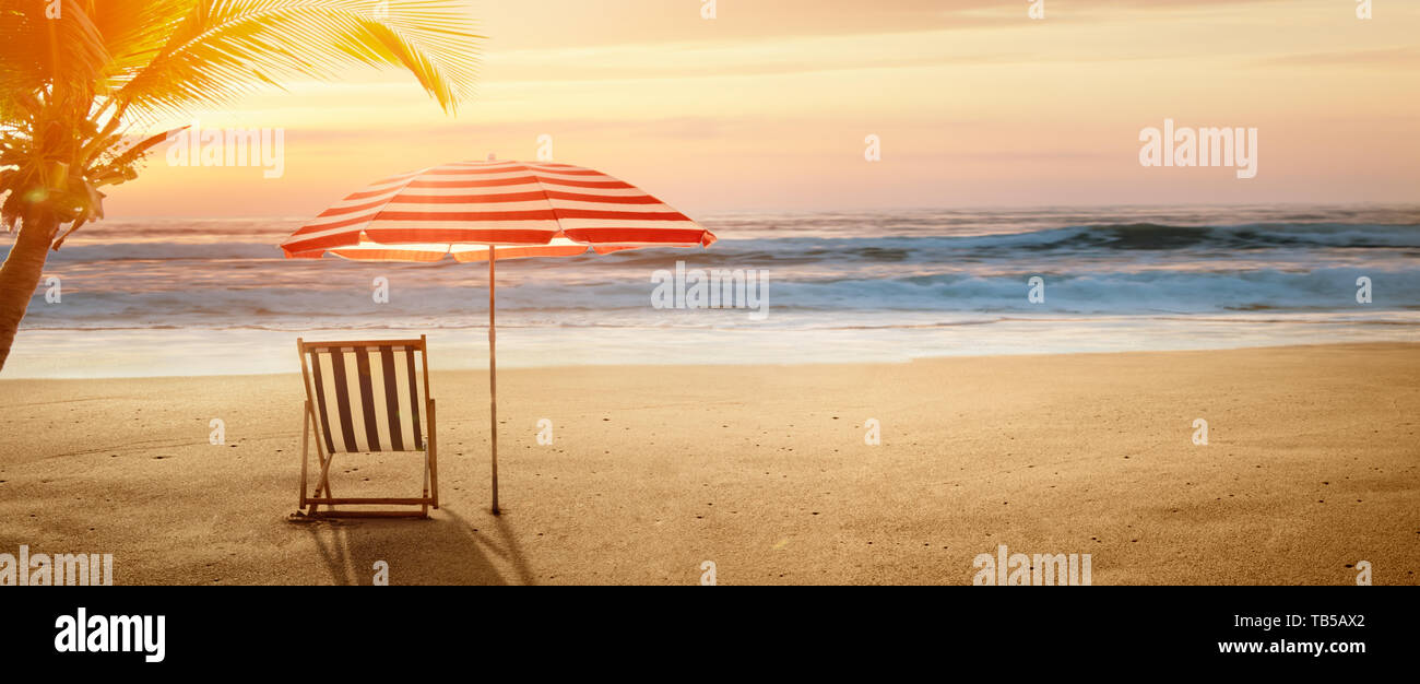 Tropical beach in sunset with beach chair and umbrella - Stock Image