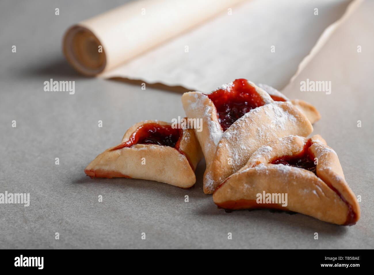 Hamantaschen for Purim holiday and the Scroll of Esther on table - Stock Image