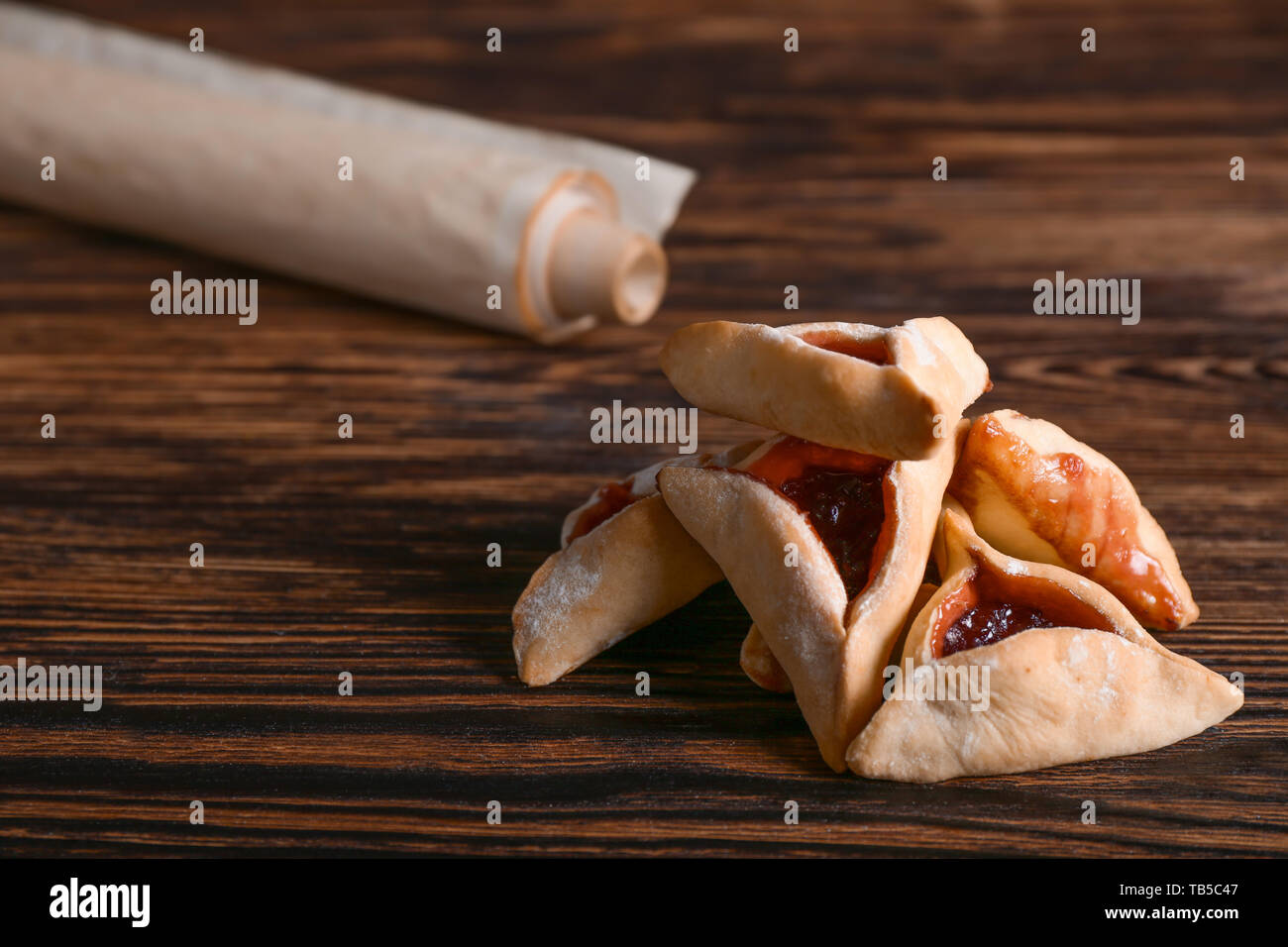 Hamantaschen and the Scroll of Esther on wooden table. Purim celebration - Stock Image