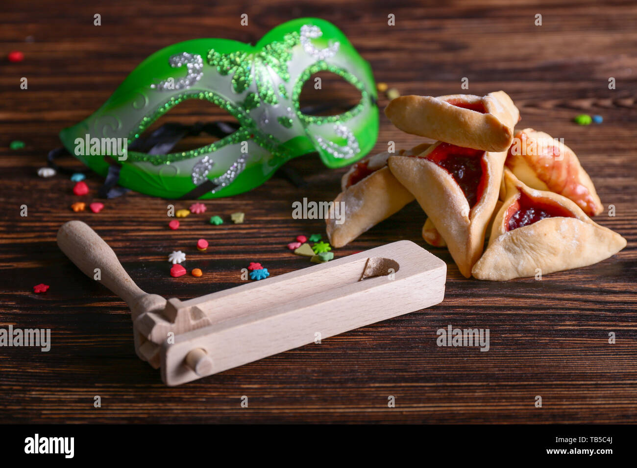 Hamantaschen, grager and mask for Purim holiday on wooden table - Stock Image