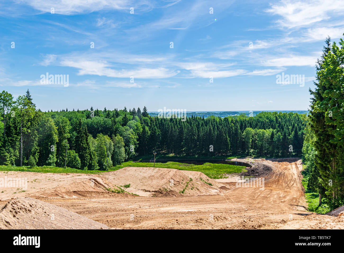 cultivated fields in countryside with dark and wet soil for agriculture. tractor made plotting furrows on the ground - Stock Image