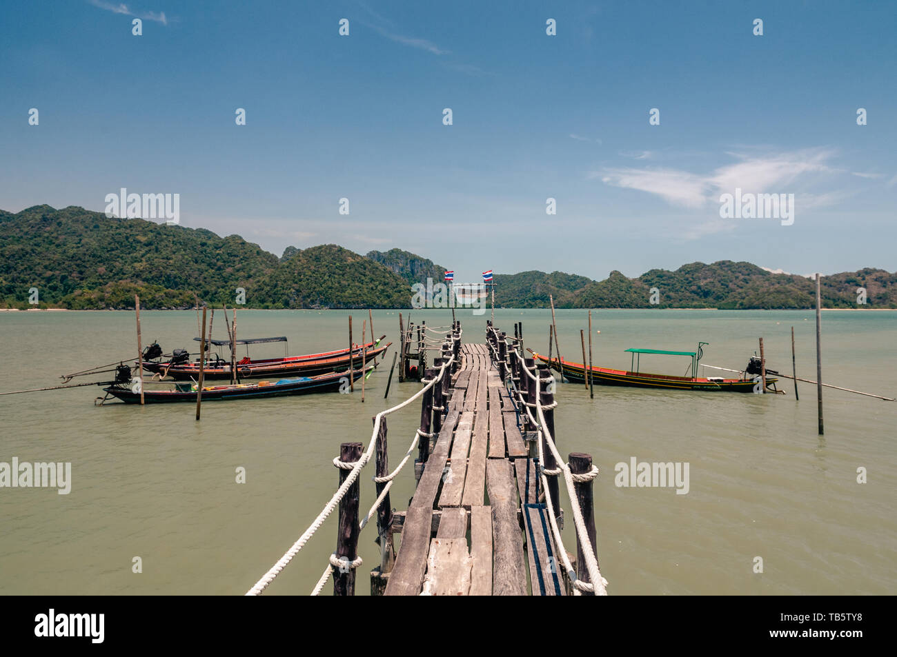 Wooden pier and thai long tail boats in Talet bay at Nakhon Si Thammarat province of Thailand. - Stock Image