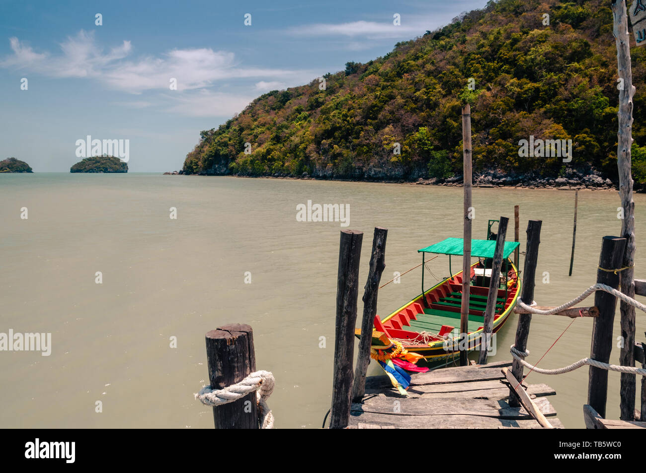 Wooden pier and thai long tail boat in Talet bay at Nakhon Si Thammarat province of Thailand. - Stock Image