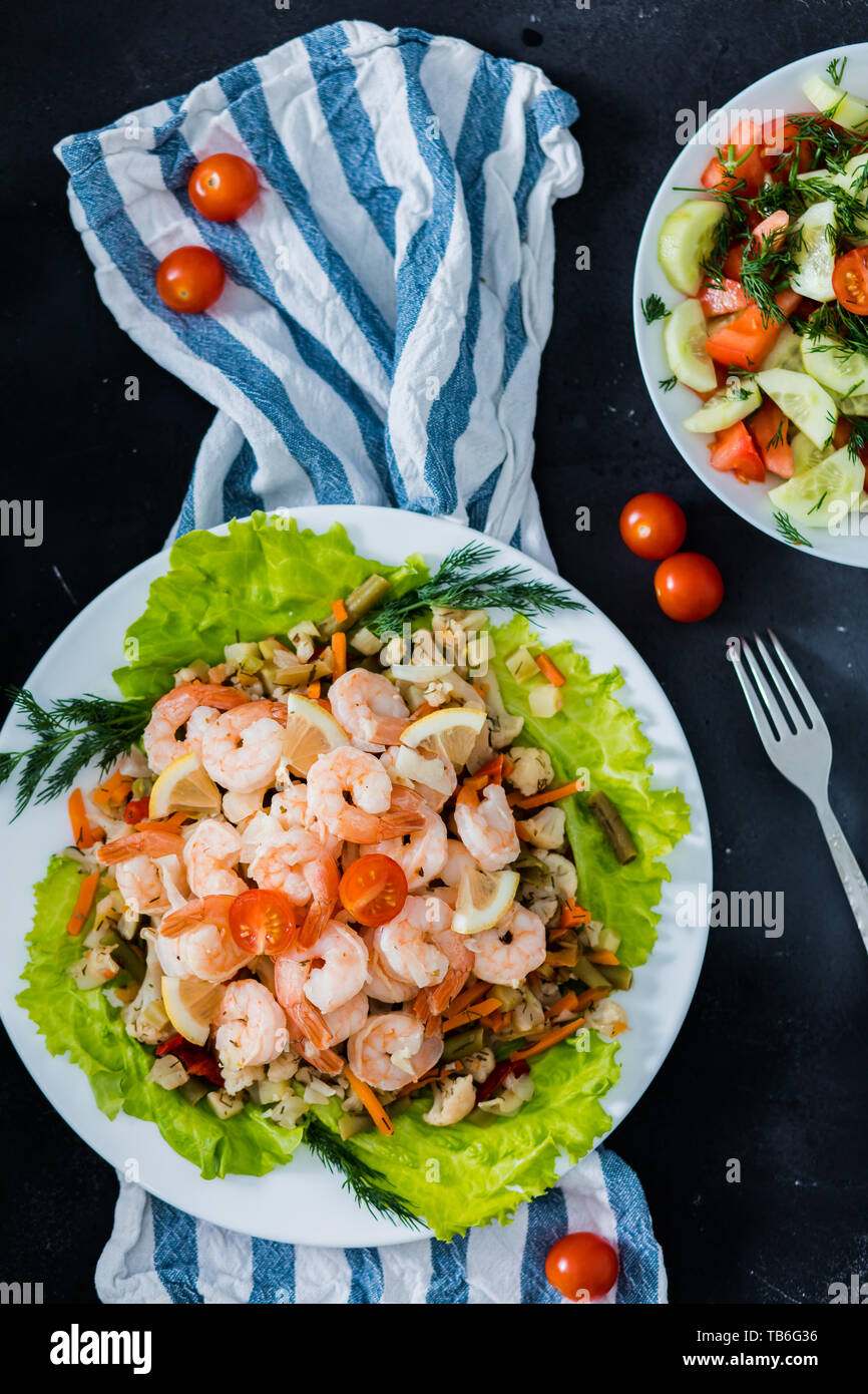 Delicious sauteed shrimp with cajun seasoning and lime on a maple plank white plate with salad and herbs on a black background, top view, closeup. Fre Stock Photo