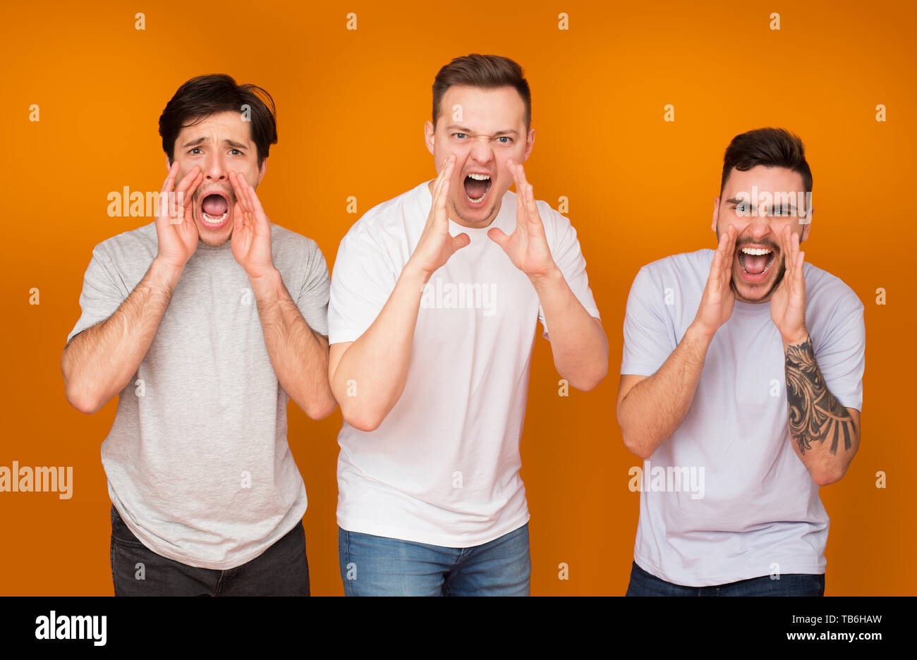Men screaming loudly, holding hands near mouth over orange studio background - Stock Image
