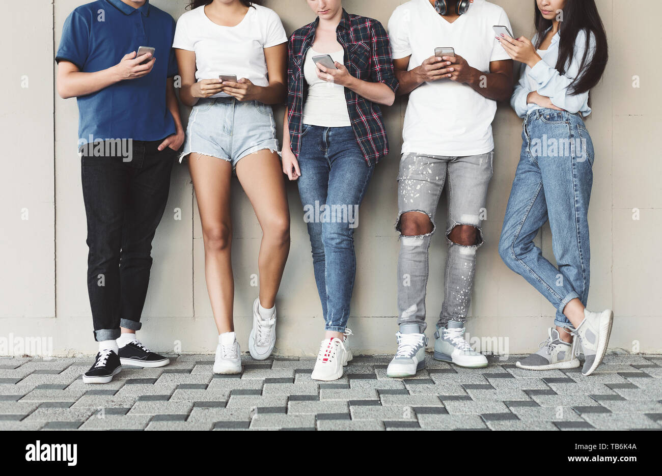 Always connected people on modern mobile phones. Group of teenagers using cellphones outdoor, free space - Stock Image