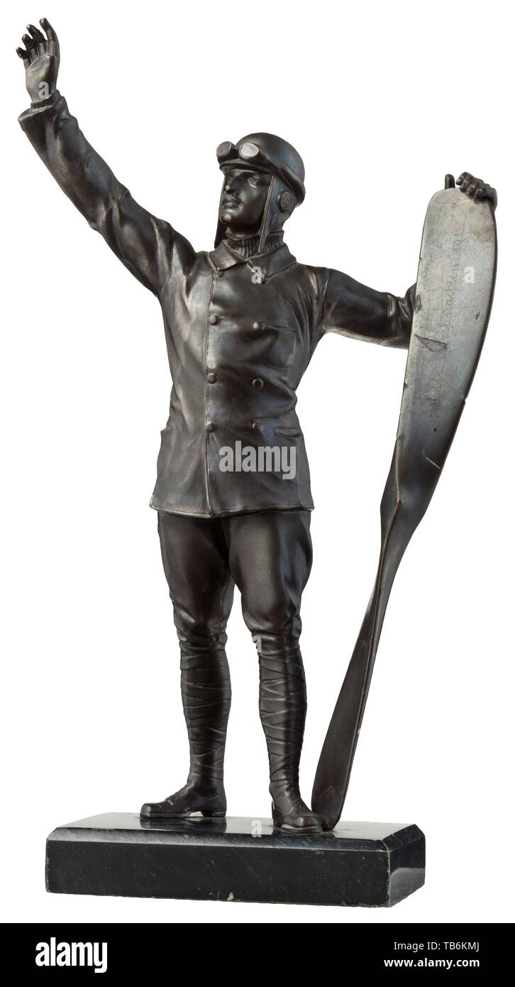 """A table decoration in the form of a pilot, Bronzed fine zinc. Detailed figure of a pilot with helmet and aviator goggles, his left hand holding a propellor, the right hand raised in greeting. The propellor blade with typical frontline engraving """"Stille Weihnachten 1915"""". On a black marble base with white veining. Total height 26.5 cm. Presumably from an officer's mess for pilots. troop, troops, armed forces, military, militaria, army, wing, group, air force, air forces, historic, historical 20th century, Editorial-Use-Only Stock Photo"""