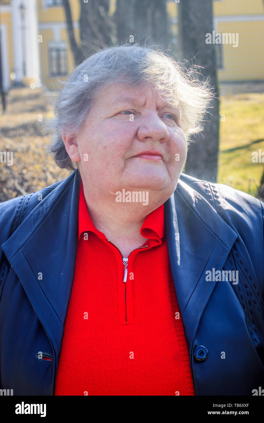 Elderly woman on a bench in the city. Grandmother in a red sweater and leather jacket. old woman Stock Photo