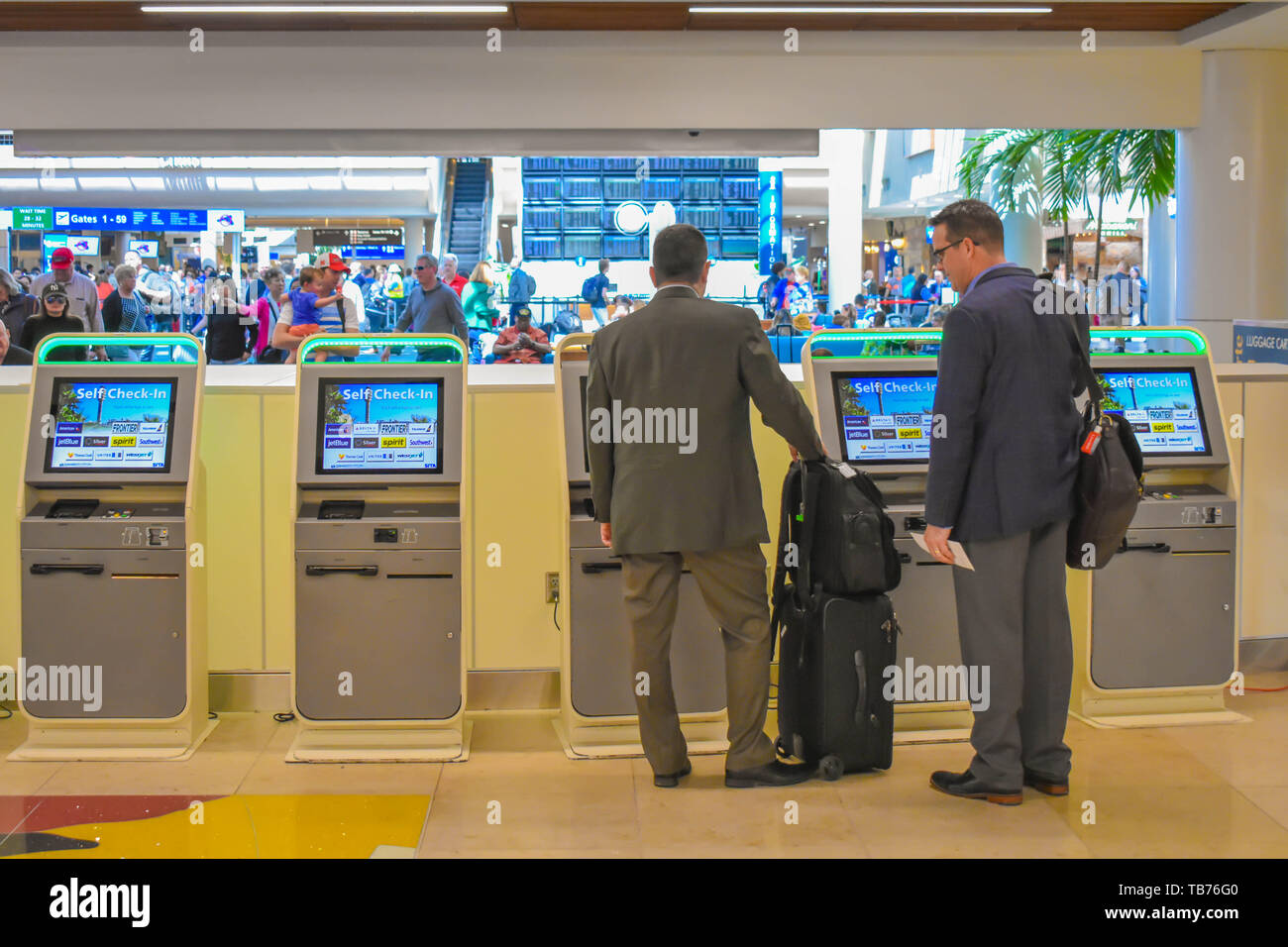 Orlando, Florida.  March 01, 2019. Businessman using Self service check-in at Orlando International Airport (1) - Stock Image