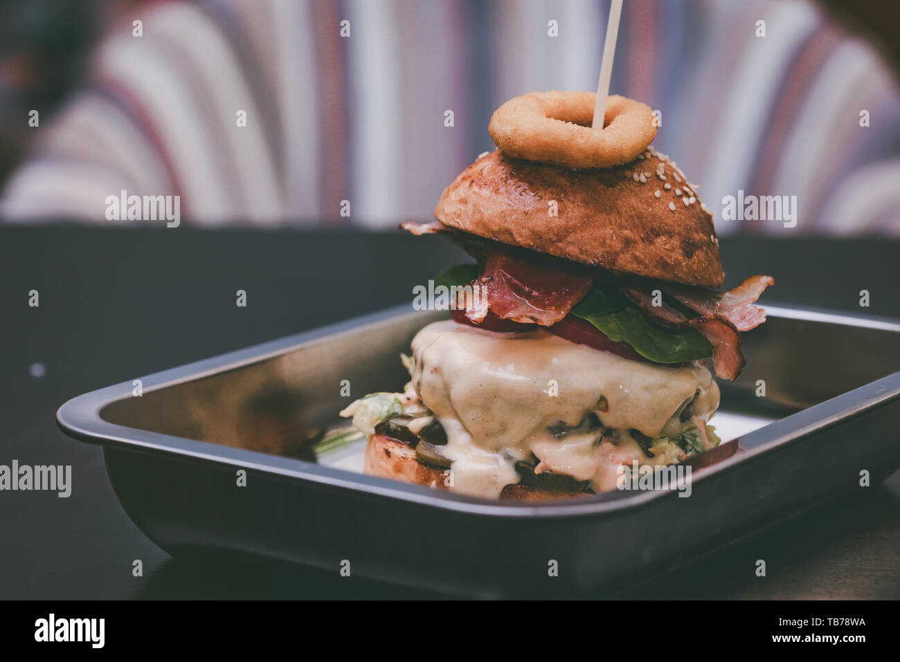 Close up tall tasty burger with cheese served on tray Stock Photo