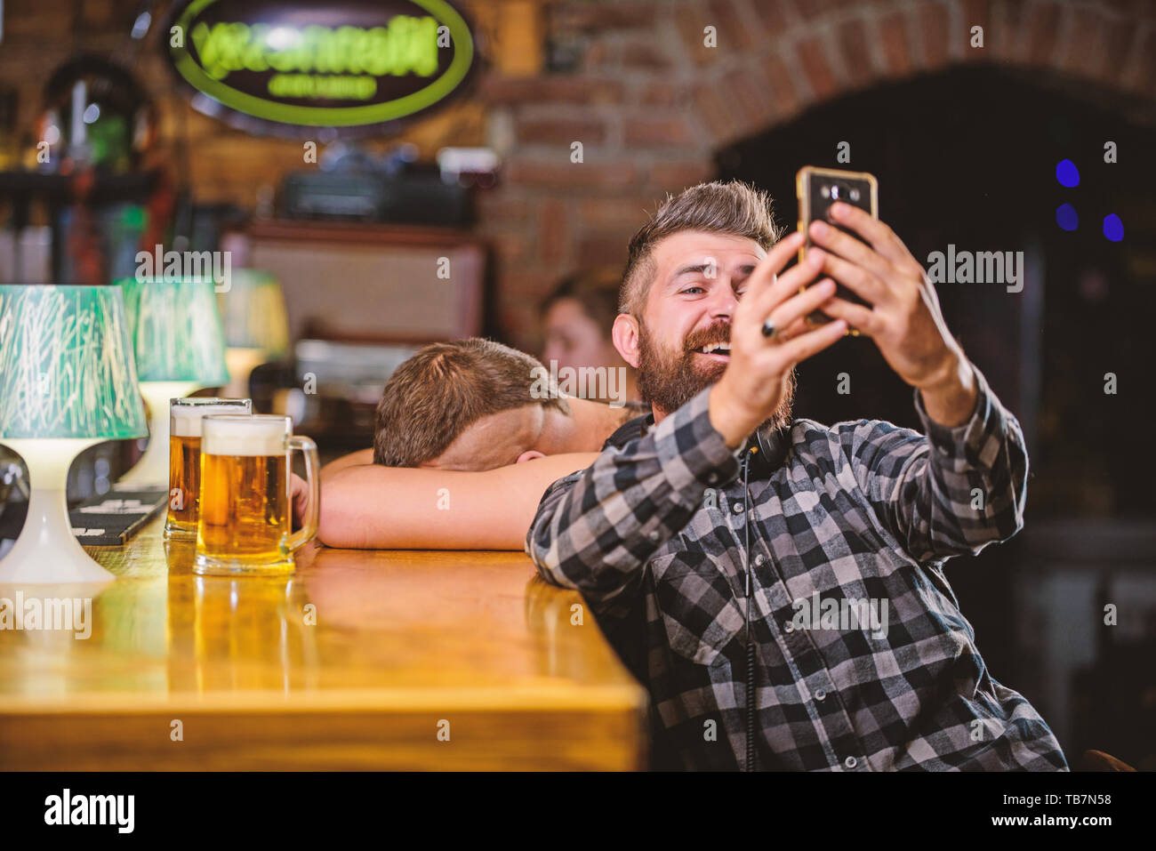 Man in bar drinking beer. Take selfie photo to remember great evening in pub. Man bearded hipster hold smartphone. Taking selfie concept. Online communication. Send selfie to friends social networks. - Stock Image